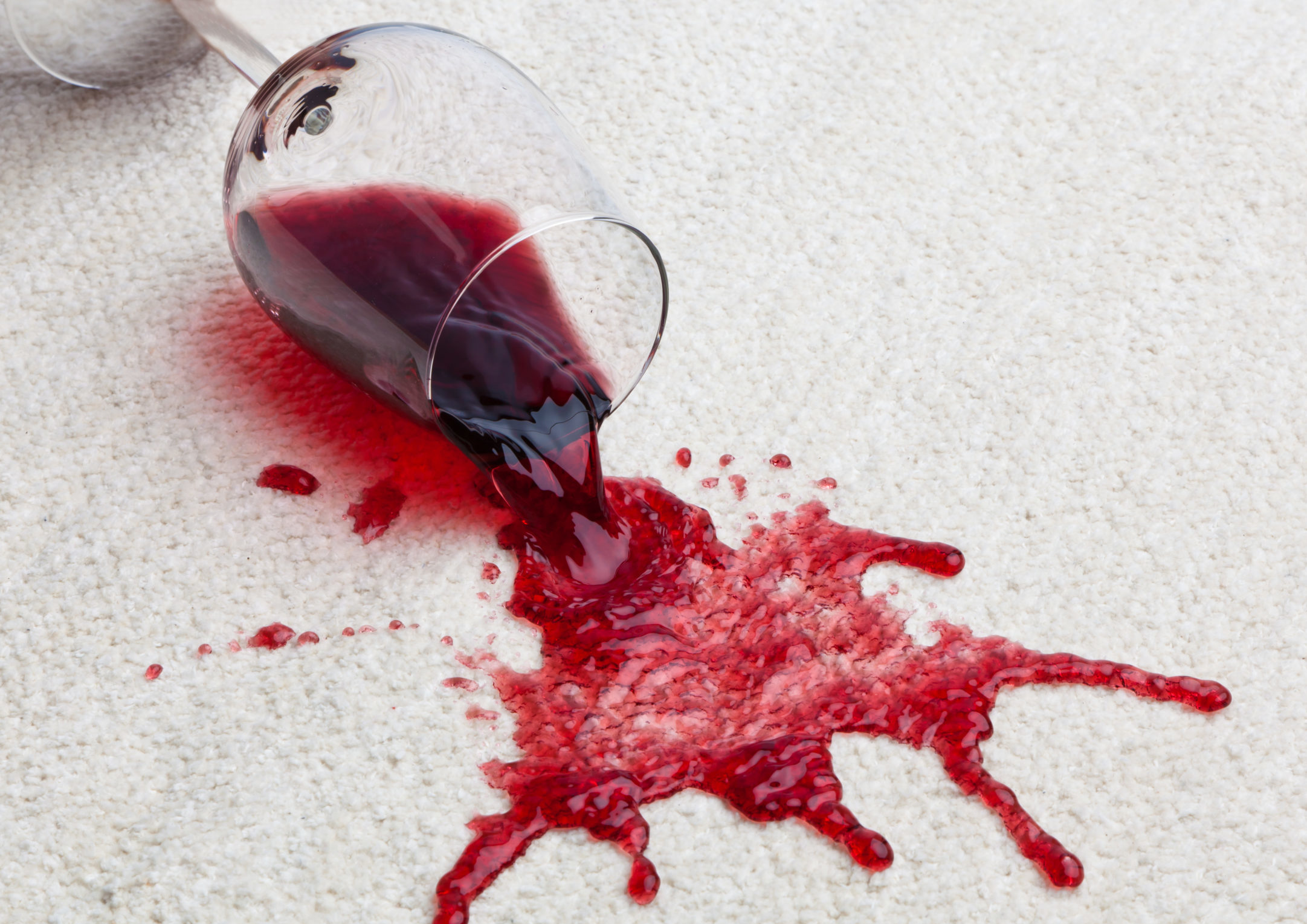 A glass of red wine spilling onto a clean white carpet