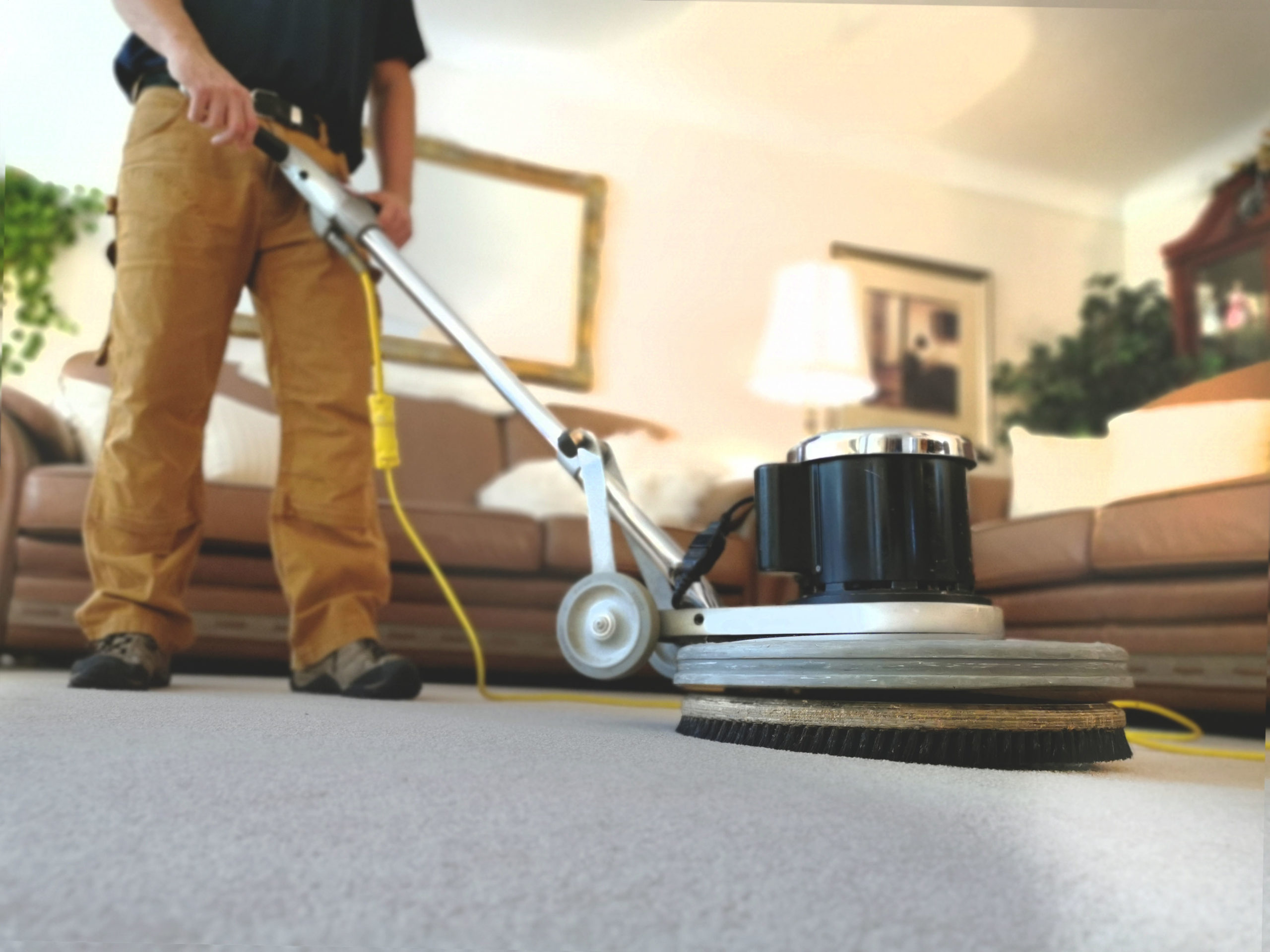 Close up of Chris O'Brien using a Rotostatic carpet cleaning scrubber in a living room