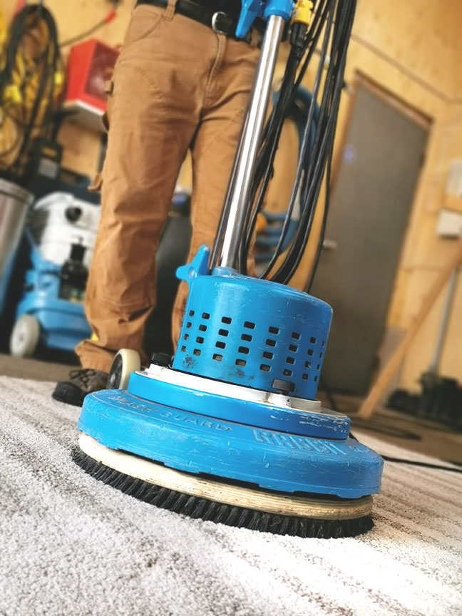 Close up of Chris O'Brien using a Rotostatic carpet cleaning scrubber in the shop